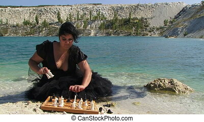 Playing chess - Woman dressed in black playing chess on a...