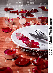 Valentine day dinner with candle and petals