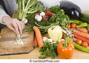 Close up woman cutting vegetables in kitchen - Close up of...