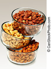 Three glass bowls filled with cashews, salted roasted almonds and honey roasted peanuts stacked.