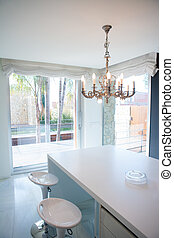 Modern white kitchen table with vintage chandelier and...
