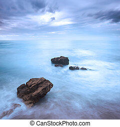 Rocks in a ocean waves under cloudy sky. Bad weather. -...
