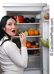 Woman eat a berry grape from fridge - Woman with open full...