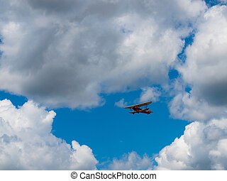 A Biplane in Flight Giving Rides in a Blue Sky and Some...