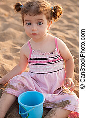 Blu eyes brunette toddler girl playing with sand in beach at...