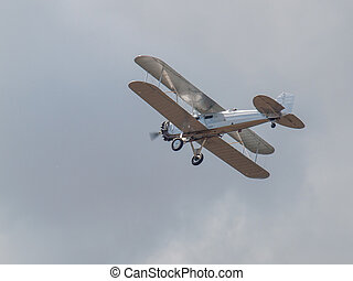 A Silver Biplane in Flight in a Blue Sky and Some Fluffy...
