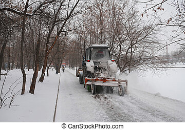 snow-removal tractor cleans alley in the park
