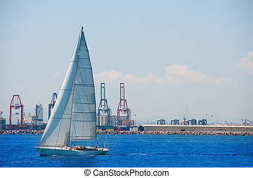 Valencia city port with sailboat and cranes in background