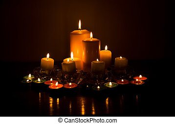 Variety of candles lights with reflection on a wood table in...