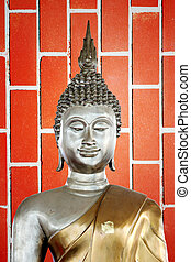 Buddha statue in the background of red Brick.