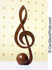 G-clef icon carved from wood on beige backgroud
