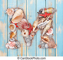 Letter M made of seashell on blue wooden background