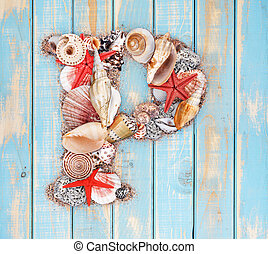 Letter P made of seashell on blue wooden background