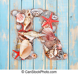 Letter R made of seashell on blue wooden background