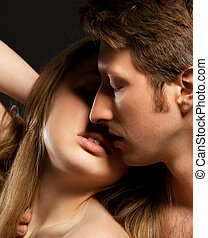 Sexy young couple kissing. Low Key photo.