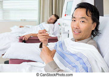 Portrait Of Patient Eating Crushed Ice During Dialysis -...
