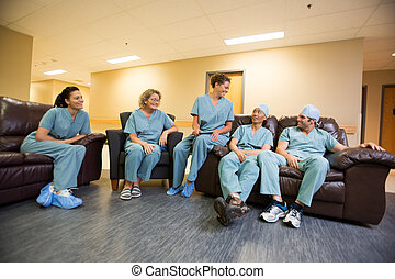 Medical Team Conversing In Hospital's Waiting Room - Full...