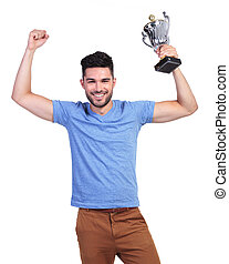 winning young casual man with a big trophy cup