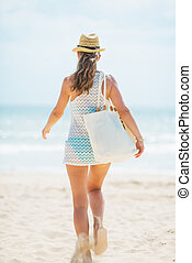 Happy young woman in hat and with bag running on beach rear...