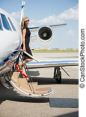 Rich Woman Disembarking Private Jet - Full length of rich...