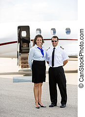 Airhostess And Pilot Standing Against Private Jet - Portrait...