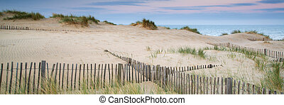 Panorama landscape of sand dunes system on beach at sunrise