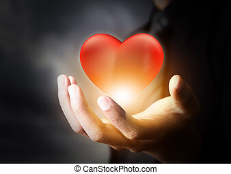 Red glass heart in businessman hand