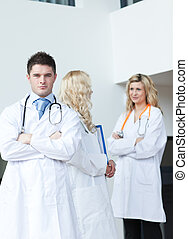 Three doctors in a hospital looking at camera