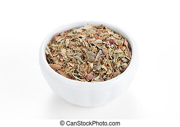 Ground dried Basil (Sweet Basil) in a white bowl on white background. Used as a spice in culinary herb all over the world. The plant is also used in medicine.