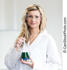 Woman in lapcoat looking at chemicals 2