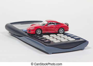Buy a new car - Calculator and red toy car isolated on white...