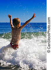 young child playing in the waves