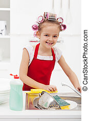 Little girl housekeeping - doing the dishes and cleaning the...