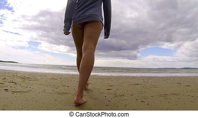 Fit woman walking into the sea on a dull day
