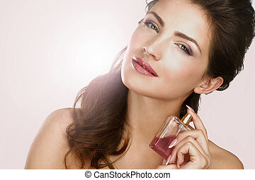 Closeup of a beautiful woman applying perfume backlight...