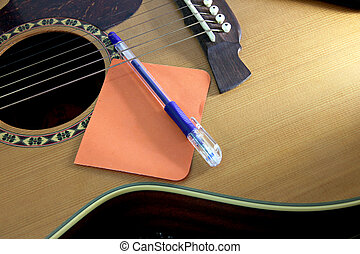Notebook orange paper and pen on the guitar. - The Picture...