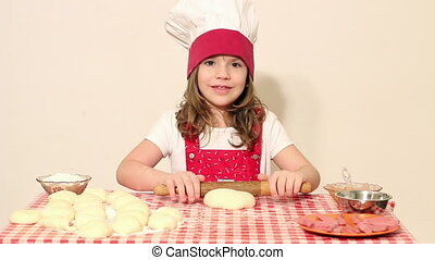 little girl cook kneading dough with rolling pin