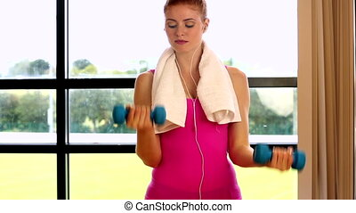 Pretty red head lifting hand weights at the gym smiling at...