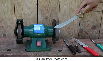 hand grinder knife - Worker hand sharpen various knives on...