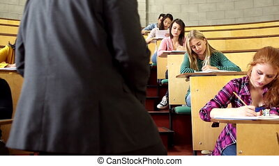 Lecturer supervising an exam in lecture hall at the...