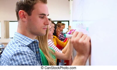 Row of focused students writing on whiteboard in classroom...
