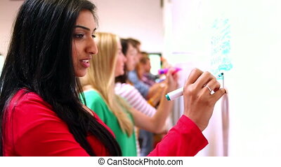 Row of focused students writing on whiteboard