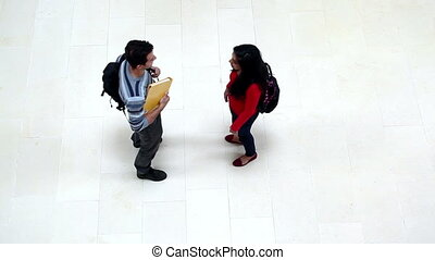 Two students chatting and hugging in the hallway at the...
