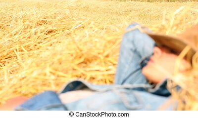Peaceful woman wearing cowboy hat lying in hay on a sunny...