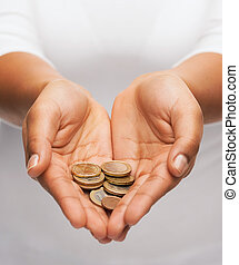 womans cupped hands showing euro coins - money and finances...