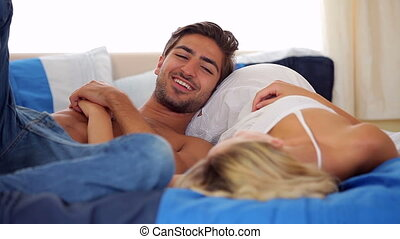 Cute young couple lying on a bed chatting at home in bedroom