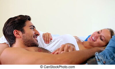 Cute young couple lying on a bed talking