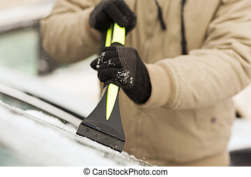 closeup of man scraping ice from car - transportation,...
