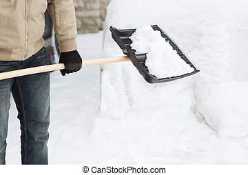 closeup of man shoveling snow from driveway - winter and...