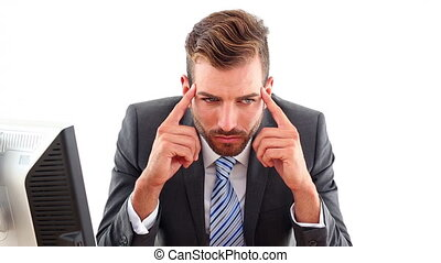 Serious businessman getting a headache at his desk in the...